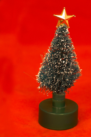 Little toy christmas tree with golden star over red backround photo