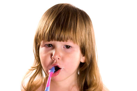 Little girl with brown eyes and blond hair cleaning her teeth isolated on white photo