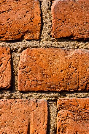 Fragment of texrured wall made of old striped red brick photo