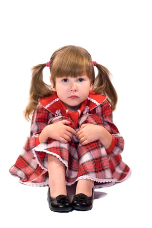 poorly: Serene worried little girl sitting on the floor in red dress isolated on white Stock Photo
