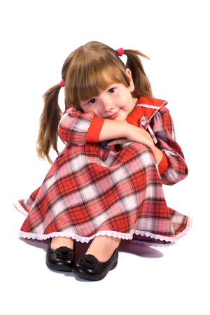 Happy little girl sitting on the floor and staring at you isolated on white photo