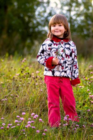 Little girl walking in the autumn meadow holding last flower in her hand photo