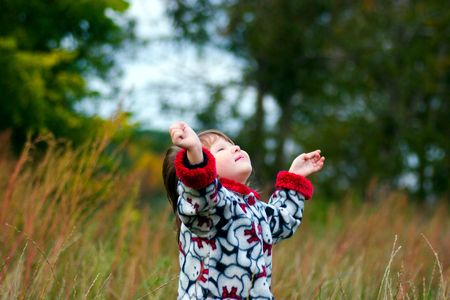 Kid looking up to the sky in the autumn meadow photo