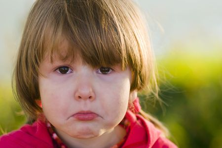 Portrait of crying little girl looking at you, tears filling her eyes, outsude