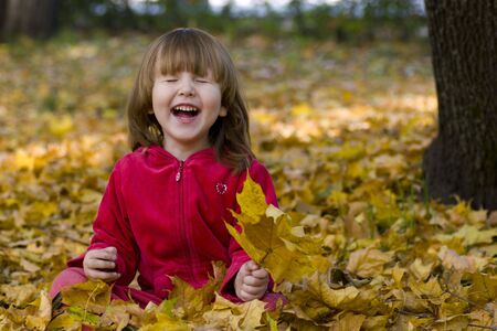 Kid laughing in the park sitting on the ground full of fallen leaves Stock Photo
