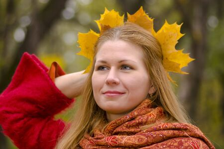 Beautiful young woman wearing maple wreath looking away with sad smile photo