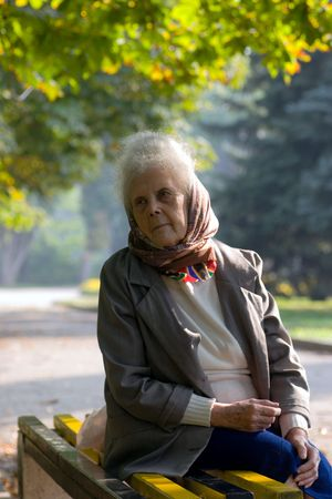 Old woman sitting on the bench in the park looking away Stock Photo - 1998087