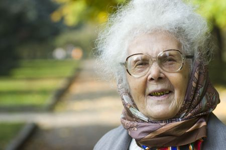 hait: Portrait of laughing elderly woman with golden teeth and grey hait wearing headscarf in park Stock Photo