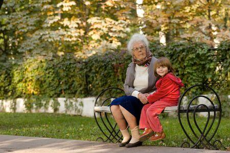 great grandmother: Gran abuela y el ni�o sentado en el banco en el parque de la mano