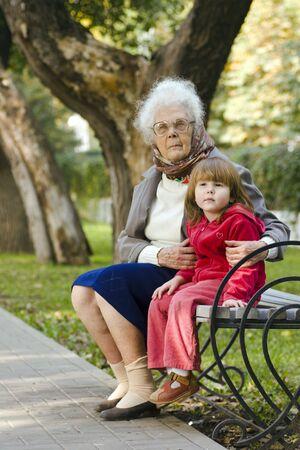 great grandmother: Gran abuela y cabrito que se sientan en el banco en el parque que mira lejos junto Foto de archivo