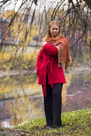 Upset woman wearing red coat standing on the bank of the river  photo