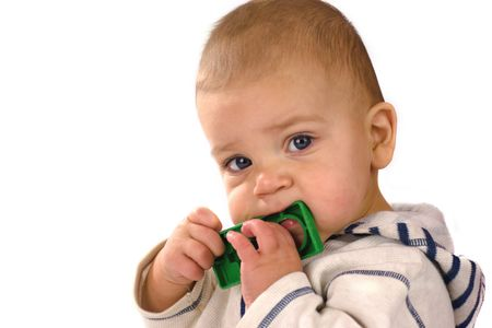 mouth pain: Baby nibbling toy cause of toothache looking at canera isolated on white