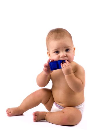 Baby chewing his blue  meccano toy because of toothache isolated on white photo