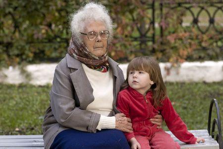 great grandmother: Gran Abuela celebraci�n nieto sentado en el banco de fuera  Foto de archivo