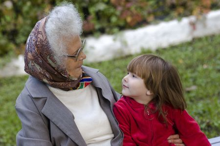 living wisdom: Great grandmother talking to her little grandchild on the bench in the park Stock Photo