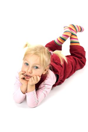 ponytails: Portrait of two years old blond pensive girl wearing red suit and ponytails lying on the floor