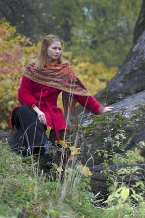 Sad woman wearing vivid red coat sitting on fallen tree looking away in the autumn park photo