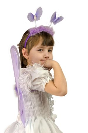 Little girl wearing fairy costume with wings looking at you with sad smile isolated on white photo