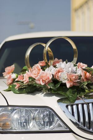 Flowers and rings by the wedding car photo