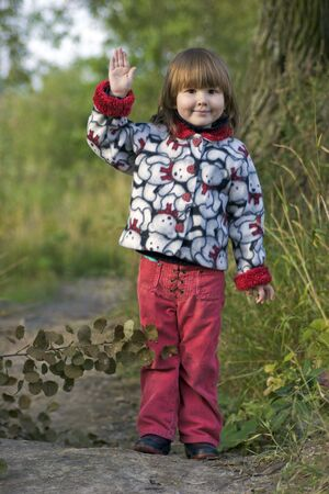 standing alone: Kid waving for goodbye standing alone before long way in the trees Stock Photo