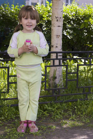 Happy girl in sportswear holding bottle with soap bubbles standing near birch tree in summer sunny day photo