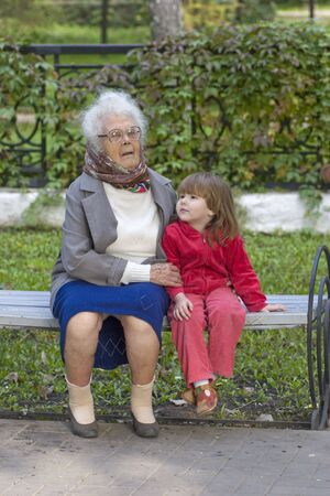 great grandmother: Gran abuela que sostiene al nieto que se sienta en los oudoors del banco