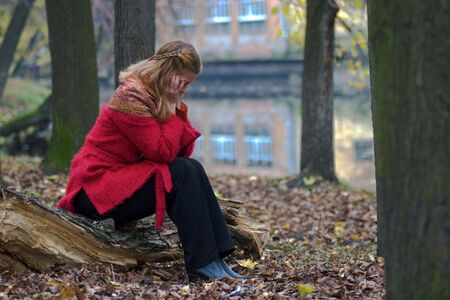 log hair: Portrait of a worried woman sitting on the fallen tree in the autumn park