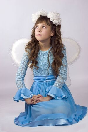Girl wearing artifical wings beautiful blue dress and white bows for a holiday sitting on a floor looking up photo