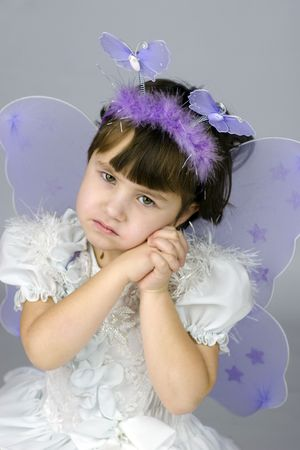 Little girl wearing fairy costume with wings looking at you with sad smile photo