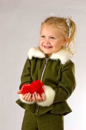 Happy smiling four years girl giving her heart as a gift  photo
