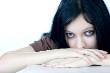 Scared teenage girl sitting near the table looking at you isolated on white photo