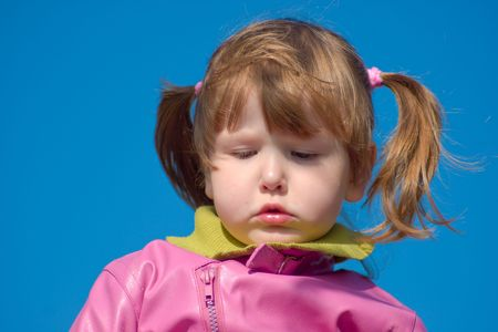 ponytails: Upset little girl looking away wearing pink coat and ponytails over deep blue sky
