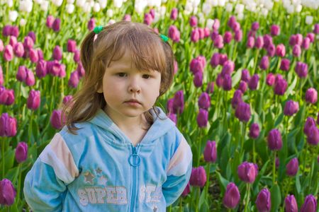 Portrait of little girl with sad face over white and purple tulips background photo