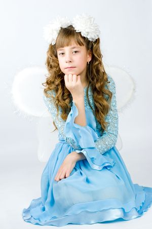 Girl wearing wings beautiful blue dress and white bows for a holiday  photo
