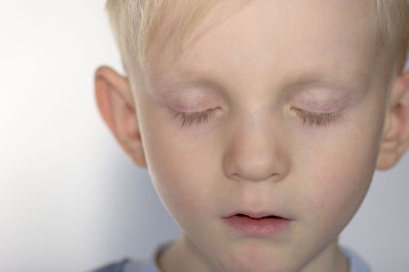Closeup portrait of Upset child with his eyes closed photo
