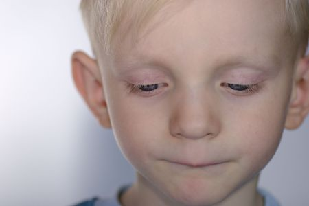 Closeup portrait of Upset child with his eyes almost closed photo