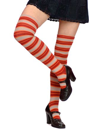 young womans legs wearing striped white orange knee-length socks and black shoes isolated on white photo