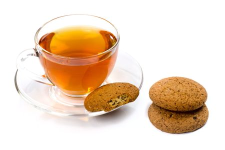 Three homemade fresh oats cookies and a cup of tea isolated on white photo
