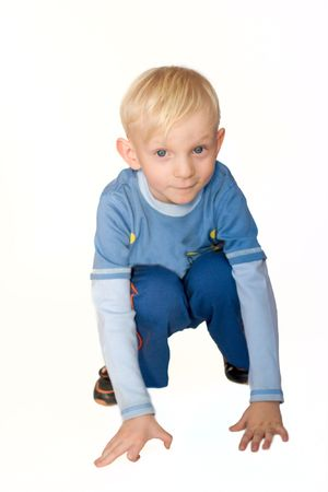 Serious boy with blond hair and blue eyes wearing casual blue closes sitting on the floor isolated photo
