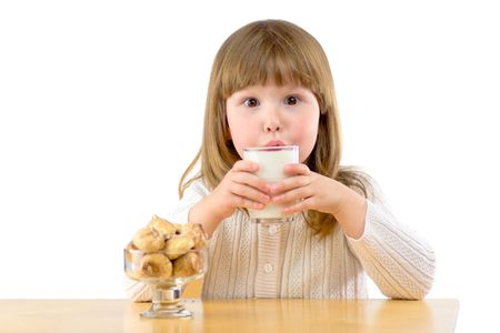 Little girl sitting at the wooden table having Breakfast isolated on white Stock Photo - 2911314