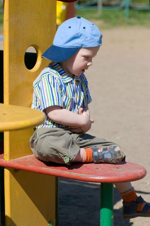 handsome Boy sitting on playground looking down  photo