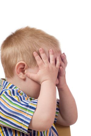 'hide out': Little boy hiding his face isolated on white