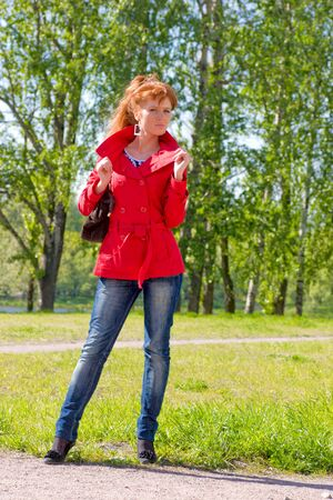 Young woman wearing jeans and red coat outdoors photo
