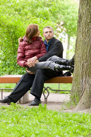 Happy young couple sitting on bench in park and talking Stock Photo - 3297772