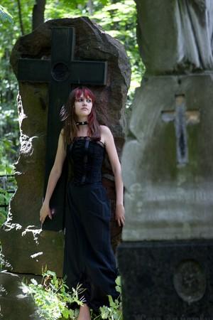 Gothic girl walking through cemetery looking away photo