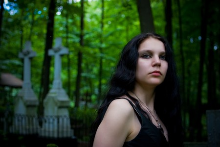 Gothic girl walking through cemetery crosses on background photo