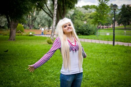 Happy young blond woman looking at you in park Stock Photo - 5101532