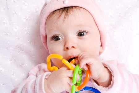 Portrait of Baby with vibrant chain toy wearing hat photo