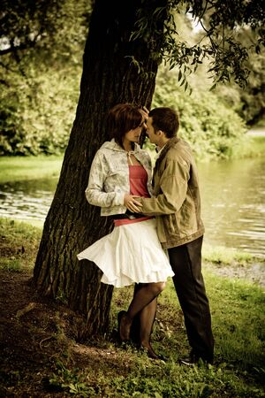 Happy young couple talking near tree in park Stock Photo - 5102010