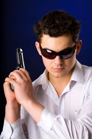 Young man wearing sunglasses holding gun over dark background photo